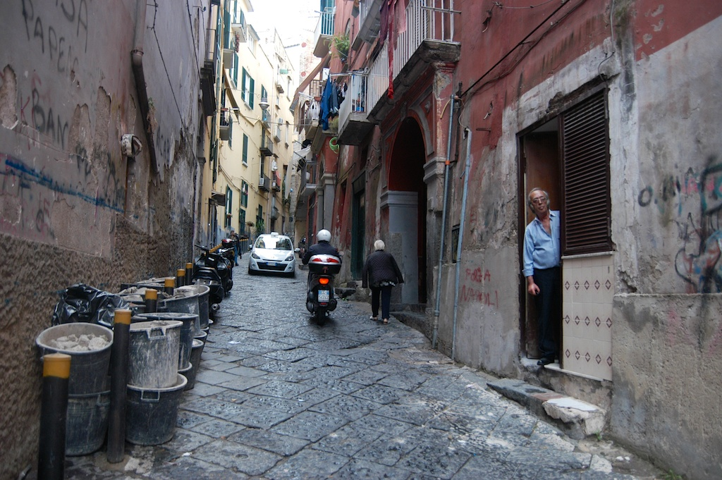 V přízemních bytech (bassi) je často jedinou možností jak pustit dovnitř světlo otevřít dveře. Všechno se tak vlastně odehrává na ulici. Neapol, Itálie.